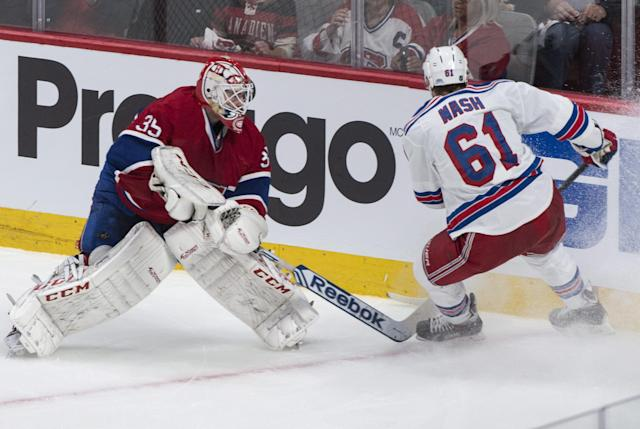 Montreal Canadiens goalie Dustin Tokarski clears the puck in the corner ahead of New York Rangers' Rick Nash during the second period of Game 5 of the NHL hockey Stanley Cup playoffs Eastern Conference finals, Tuesday, May 27, 2014, in Montreal. (AP Photo/The Canadian Press, Paul Chiasson)