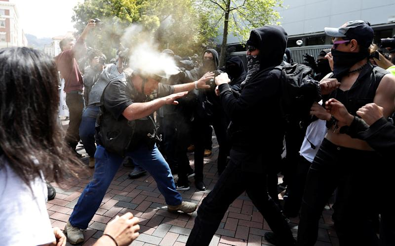 A Trump supporter is pepper sprayed by a group on counter-protesters during a rally in Berkeley - Credit: Reuters