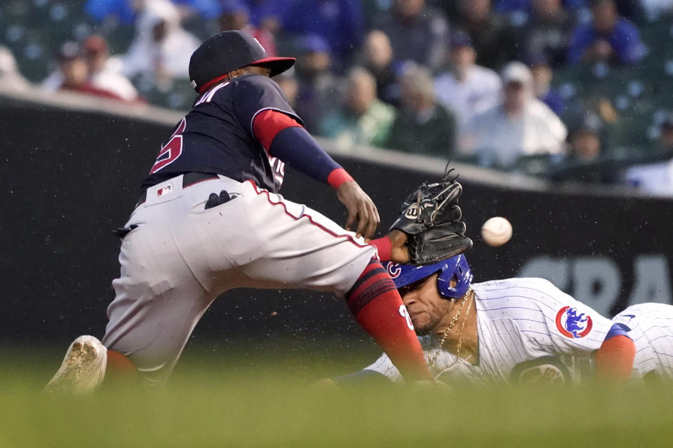Chicago Cubs' Willson Contreras, right, slides in to second as Washington Nationals second baseman Josh Harrison waits for the throw during the third inning of a baseball game Tuesday, May 18, 2021, in Chicago. Contreras was originally ruled safe with a steal, but the call was overturned on review. (AP Photo/Charles Rex Arbogast)