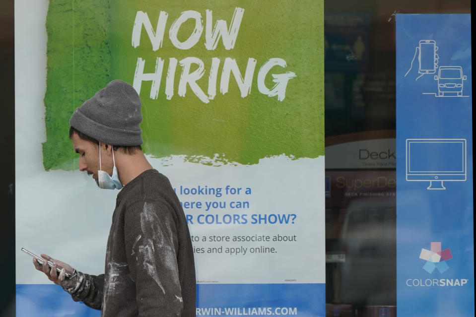 """A man walks past a """"Now Hiring"""" sign on a window at Sherwin Williams store, Friday, Feb. 26, 2021, in Woodmere Village, Ohio. Massive fraud in the nation's unemployment system is raising alarms even as President Joe Biden and Congress prepare to pour hundreds of billions more into expanded benefits for those left jobless by the coronavirus pandemic. (AP Photo/Tony Dejak)"""