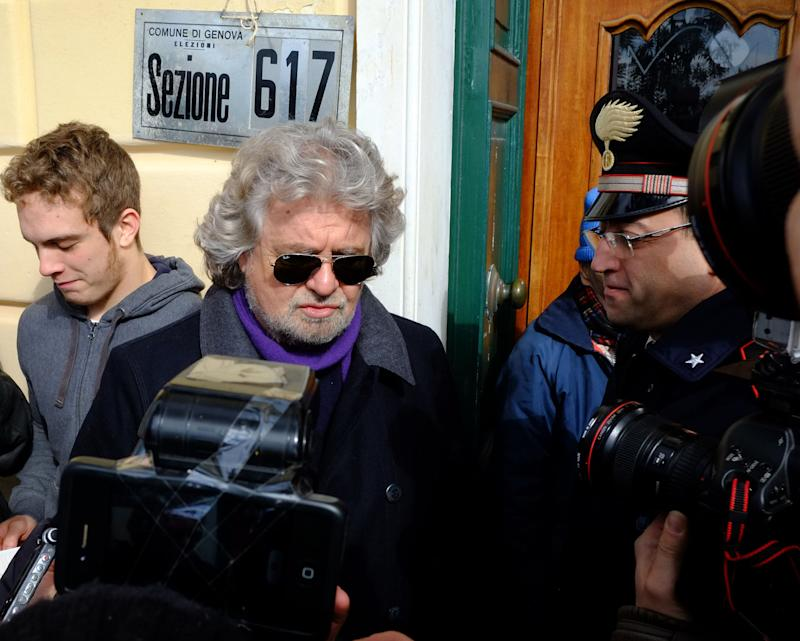 Comic-turned-politician Beppe Grillo, center, is photographed as he arrives at his polling station to cast his vote, in Genoa, Italy, Monday, Feb. 25, 2013. Italians voted for a second day Monday in a national election that will determine whether they are prepared to stay the course of painful economic reform or send a message of discontinuity to the political class that led the country to the brink of disaster by rallying around a protest party. (AP Photo/Fabio Palli, Lapresse)  ITALY OUT