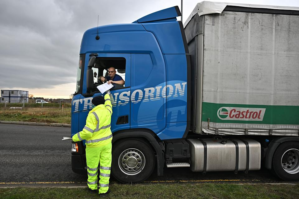 "A traffic marshall checks the documents of a freight lorry driver at Waterbrook Park facility in Ashford, south east England on January 15, 2021, as hauliers get used to life under the post-Brexit trade deal. - British companies are struggling with a large amount of red tape as a result of Brexit, with senior government minister Michael Gove recently admitting that there would be ""significant disruption"" at the border because of increased bureaucracy that is slowing the flow of freight. (Photo by BEN STANSALL / AFP) (Photo by BEN STANSALL/AFP via Getty Images)"