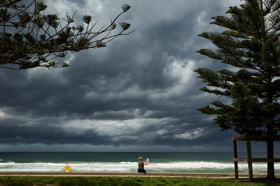 A lady takes a photo of an approaching storm at Manly Beach in Sydney, Australia.