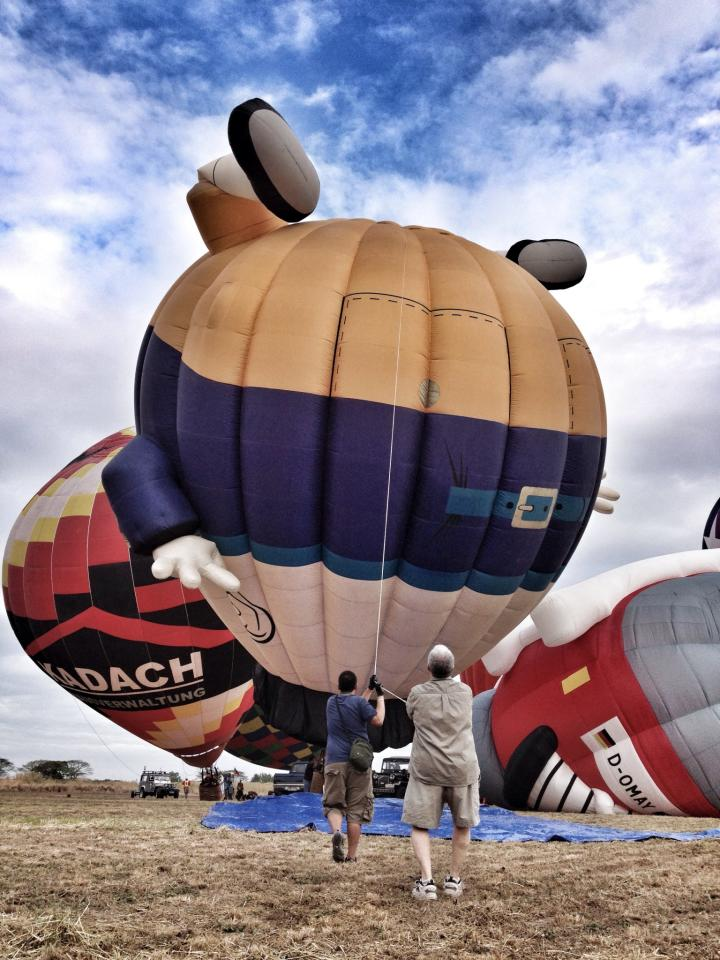 PUSH & PULL. The pilots try to control the balloon's movement to make sure it will not fly out and withstand the movement of air during the 18th Philippine International Hot Air Balloon Fiesta at Clark Field, Pampanga, Feb. 21, 2013. (Photo courtesy of Rolan Garcia)