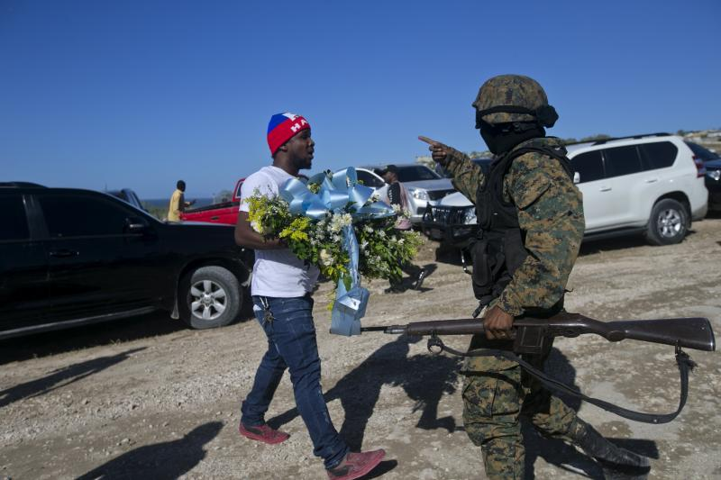 A national police officer stops a man who tries to place flowers at Titanyen, a mass burial site, as Haiti's President Jovenel Moise attends a memorial service honoring the victims of the 2010 earthquake in Port-au-Prince, Haiti, Sunday, Jan. 12, 2020. Sunday marks the 10th anniversary of the devastating 7.0 magnitude earthquake that destroyed an estimated 100,000 homes across the capital and southern Haiti, including some of the country's most iconic structures. (AP Photo/Dieu Nalio Chery)