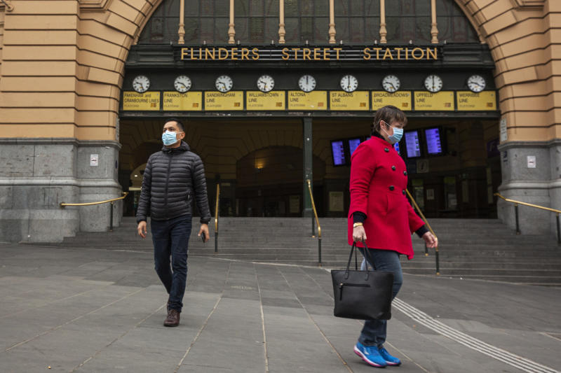 People wearing face masks in front of Melbourne's Flinders Street Station in Melbourne.