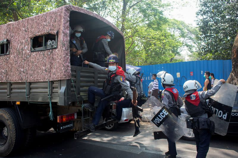 Riot police officers get on a police vehicle during a rally against the military coup, in Yangon