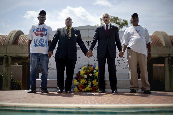 """FILE - In this April 4, 2012, file photo, civil rights activists and Southern Christian Leadership Conference members from left, Ralph Worrell, Dr. Bernard Lafayette Jr., C.T. Vivian and Frederick Moore, join hands and sing """"We Shall Overcome"""" at the Atlanta gravesite of the Rev. Martin Luther King Jr., marking the 44th anniversary of his assassination. This Sunday, March 7, 2021, marks the 56th anniversary of the Selma marches and """"Bloody Sunday,"""" when more than 500 demonstrators gathered on March 7, 1965, to demand the right to vote and cross Selma's Edmund Pettus Bridge. (AP Photo/David Goldman, File)"""