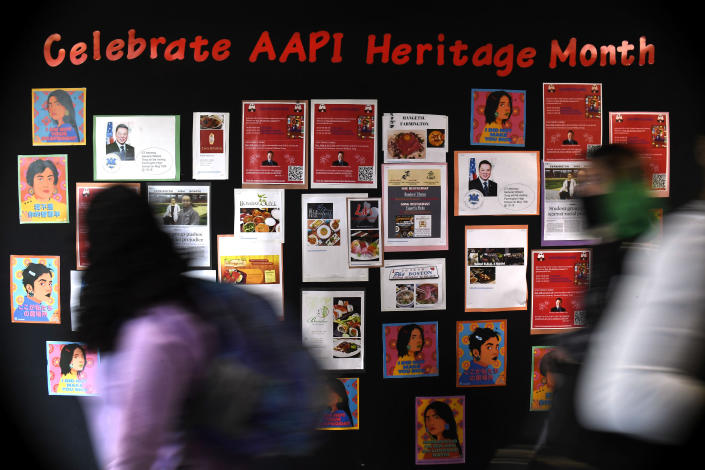 In this Monday, May 10, 2021 students walk past a display for Asian Pacific American Heritage Month at Farmington High School in Farmington, Conn. The year of anti-Asian violence has led students and teachers to advocate for reexamining how Asian American studies and history are taught in public schools. (AP Photo/Jessica Hill)