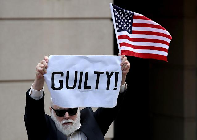 A lone protester holds up a sign and American flag outside the Albert V. Bryan United States Courthouse after former Trump campaign chairman Paul Manafort was found guilty on eight counts of fraud August 21, 2018 in Alexandria, Virginia.