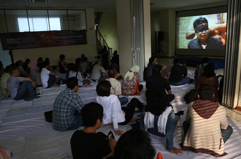 """In this Monday, Sept. 30, 2013 photo, people watch documentary film """"The Act of Killing"""" in Jakarta, Indonesia. The new American-directed documentary challenges widely held views about hundreds of thousands of deaths carried out across Indonesia from 1965 to 1966 in the name of fighting communism. It explores the country's darkest open secret by allowing former mass killers to re-enact their horrors on screen. (AP Photo/Tatan Syuflana)"""