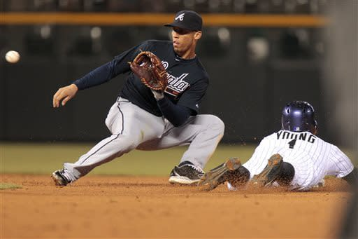 Colorado Rockies' Eric Young Jr. (1) steals second while Atlanta Braves shortstop Andrelton Simmons (19) waits for the throw during the fifth inning of the second baseball game of a doubleheader Tuesday, April 23, 2013 in Denver. (AP Photo/Barry Gutierrez)