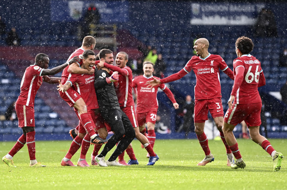 Liverpool's goalkeeper Alisson celebrates with teammates after scoring his side's second goal during the English Premier League soccer match between West Bromwich Albion and Liverpool at the Hawthorns stadium in West Bromwich, England, Sunday, May 16, 2021. (Laurence Griffiths/Pool via AP)