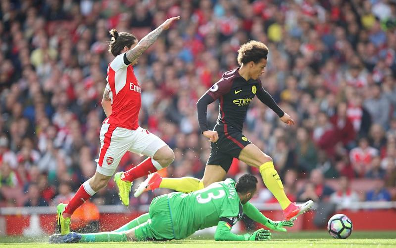Leroy Sane skips away from Hector Bellerin and around David Ospina to score the opener - Credit: REX FEATURES