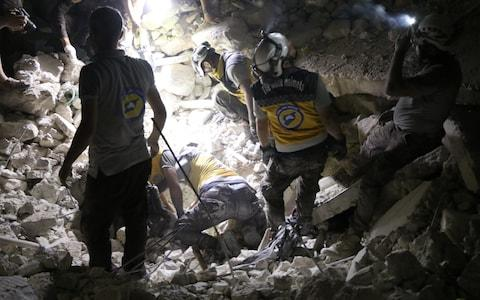 Civil defense members carry out search and rescue works after the airstrikes in Idlib province - Credit: Anadolu