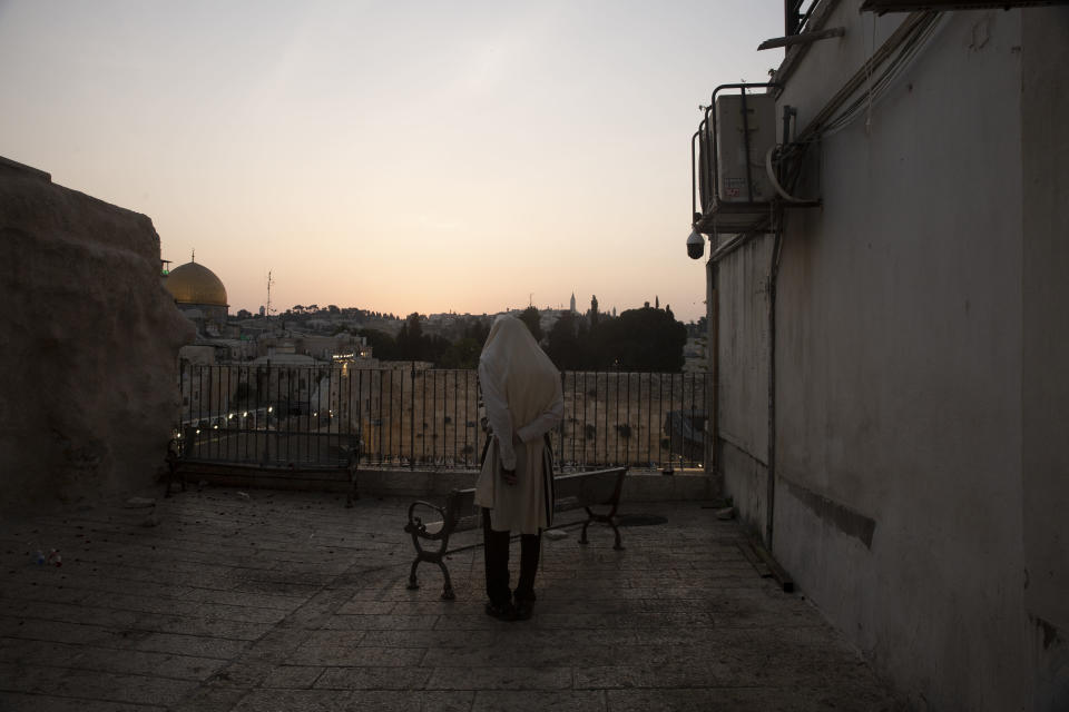 A Jewish man prays overlooking the Western Wall, the holiest site where Jews can pray, and the Mughrabi Bridge, a wooden pedestrian bridge connecting the wall to the Al Aqsa Mosque compound, in Jerusalem's Old City, Tuesday, July 20, 2021. The rickety bridge allowing access to Jerusalem's most sensitive holy site is at risk of collapse, according to experts. But the flashpoint shrine's delicate position at ground-zero of the Israeli-Palestinian conflict has prevented its repair for more than a decade. (AP Photo/Maya Alleruzzo)