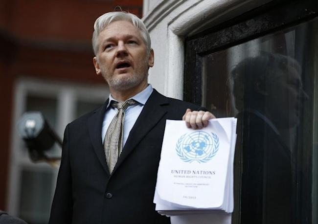 WikiLeaks founder Julian Assange holds a copy of a U.N. ruling as he makes a speech from the balcony of the Ecuadorian Embassy, in central London, Britain February 5, 2016. REUTERS/Peter Nicholls