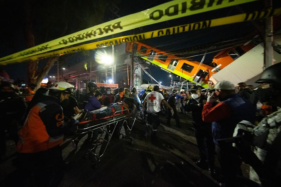 The injured are carried by stretcher away from the scene of a raised subway track that collapsed.
