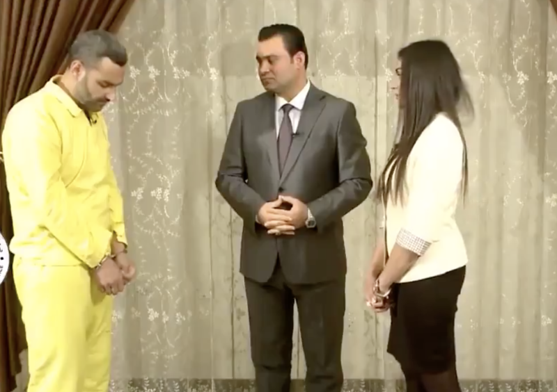 In a yellow jump suit, the prisoner stand with a TV presenter and his former victim.