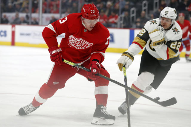 Detroit Red Wings left wing Adam Erne (73) shoots the puck past Vegas Golden Knights defenseman Nick Holden (22) during the first period of an NHL hockey game, Sunday, Nov. 10, 2019, in Detroit. (AP Photo/Carlos Osorio)