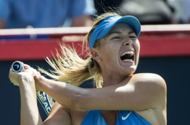Maria Sharapova of Russia yells as she returns to Garbine Muguruza of Spain at the Rogers Cup tennis tournament Wednesday Aug. 6, 2014 in Montreal. (AP Photo/The Canadian Press, Paul Chiasson)
