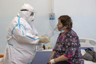 "Dr. Tatyana Symbelova treats a coronavirus patient on artificial lung respiration at an intensive care unit in the red zone of the hospital in Ulan-Ude, the regional capital of Buryatia, a region near the Russia-Mongolia border, Russia, Friday, Nov. 20, 2020. Symbelova told the AP that as the number of patients rose, her hospital kept adding beds — ""in the corridor, in the outpatient ward next door"" — but ""the situation, still, grew worse and worse."" (AP Photo/Anna Ogorodnik)"
