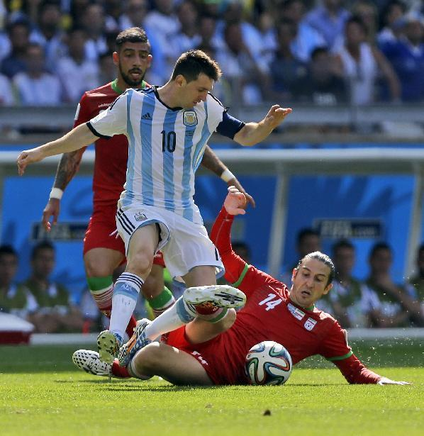 Argentina's Lionel Messi gets tangled with Iran's Andranik Teymourian during the group F World Cup soccer match between Argentina and Iran at the Mineirao Stadium in Belo Horizonte, Brazil, Saturday, June 21, 2014. (AP Photo/Fernando Vergara)