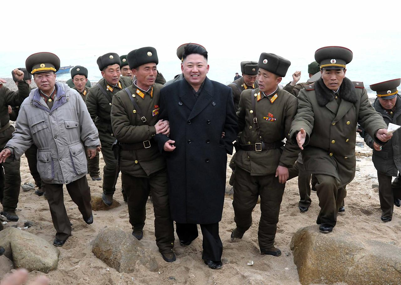 In this March 7, 2013 photo released by the Korean Central News Agency (KCNA) and distributed March 8, 2013 by the Korea News Service, North Korean leader Kim Jong Un, center, walks with military personnel as he arrives for a military unit on Mu Islet, located in the southernmost part of the southwestern sector of North Korea's border with South Korea. Seven years of U.N. sanctions against North Korea have done nothing to derail Pyongyang's drive for a nuclear weapon capable of hitting the United States. They may have even bolstered the Kim family by giving their propaganda maestros ammunition to whip up anti-U.S. sentiment and direct attention away from government failures. (AP Photo/KCNA via KNS) JAPAN OUT UNTIL 14 DAYS AFTER THE DAY OF TRANSMISSION