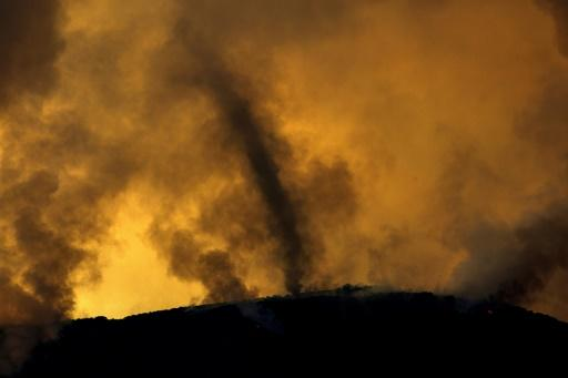 A whirlwind of ash rises from a ridge at a fire near Lake Elsinore in southern California