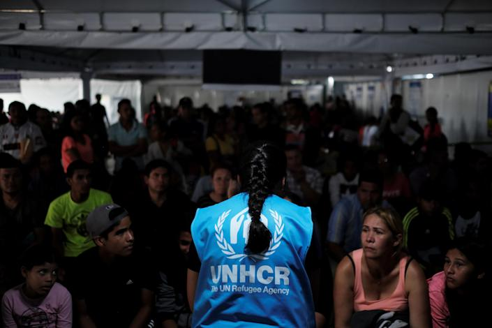<p>A member of United Nations High Commissioner for Refugees (UNHCR) talks with Venezuelans as they queue in line to receive a vaccine after showing their passports or identity cards at the Pacaraima border control, Roraima state, Brazil, Aug. 8, 2018. (Photo: Nacho Doce/Reuters) </p>