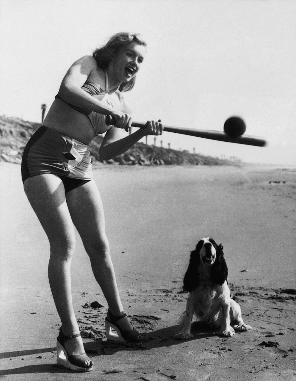 """<p>Marilyn Monroe plays softball on the beach with a pup by her side, circa 1950. </p><p><strong>Related: <a href=""""https://www.esquire.com/lifestyle/g15897154/celebrity-beach-photos-vintage/"""" rel=""""nofollow noopener"""" target=""""_blank"""" data-ylk=""""slk:Vintage Photos of Celebrities at the Beach"""" class=""""link rapid-noclick-resp"""">Vintage Photos of Celebrities at the Beach</a></strong></p>"""