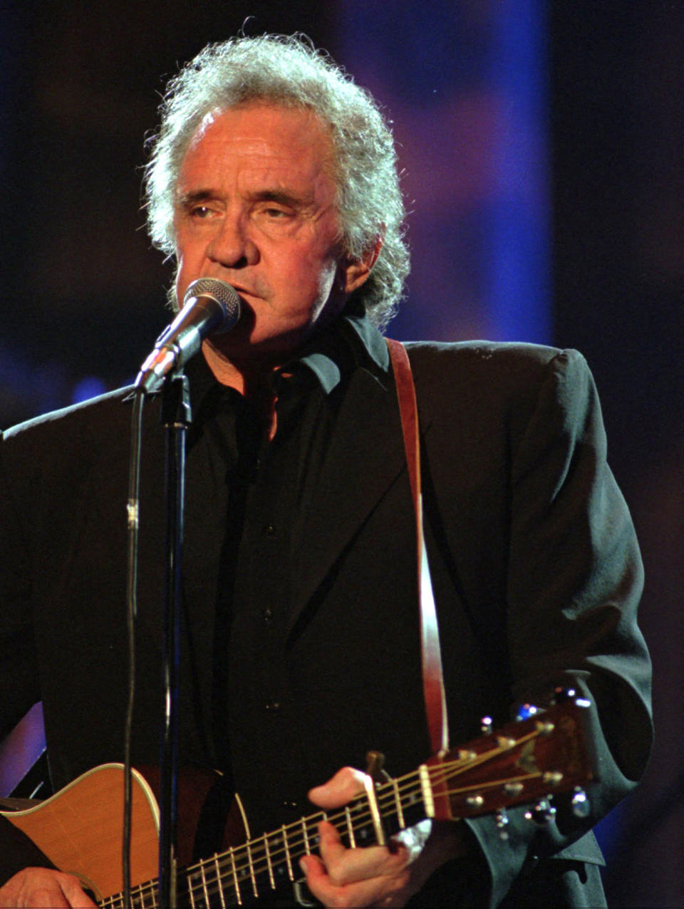 """FILE - In this Sept. 2, 1995, file photo, singer Johnny Cash performs during his segment of the Concert for the Rock and Roll Hall of Fame, in Cleveland. The Man in Black is about to get his own day in Arkansas. The Arkansas House on Tuesday, April 20, 2021, gave unanimous final approval to a bill that would make Feb. 26 """"Johnny Cash Day,"""" sending it to Gov. Asa Hutchinson, who plans to sign it. (AP Photo/Mark Duncan, File)"""