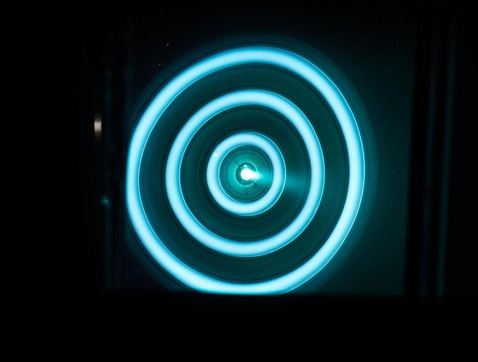 A head-on shot of the X3 ion thruster firing at 50 kilowatts, viewed through a warped mirror in the vacuum chamber. <cite>NASA</cite>