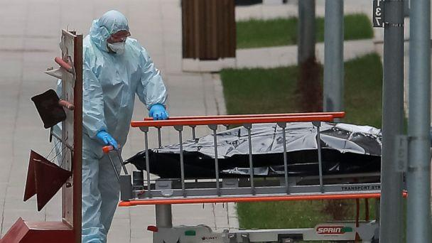 PHOTO: A medical specialist wearing protective gear pulls a stretcher toward an ambulance while relocating a bag, which presumably contains a human body, outside a hospital for patients infected with coronavirus on the outskirts of Moscow, April 20, 2020. (Maxim Shemetov/Reuters)
