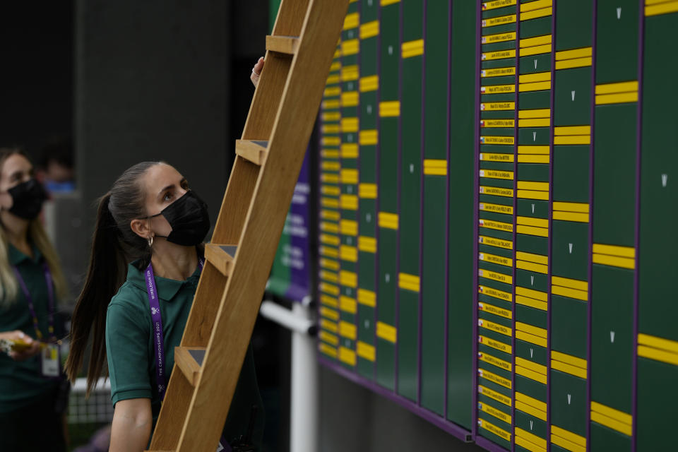 A member of staff places information on the scoreboard in the grounds of the Wimbledon Tennis Championships in London, Thursday July 1, 2021. (AP Photo/Alastair Grant)