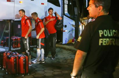 A Brazilian federal policeman stands guard as Germany's national soccer team players (2nd R-L) Mats Hummels, Bastian Schweinsteiger and Kevin Grosskreutz leave a bus to take a ferry in the town of Santa Cruz Cabralia, north of Porto Seguro June 16, 2014. REUTERS/Arnd Wiegmann (BRAZIL - Tags: SPORT SOCCER WORLD CUP)