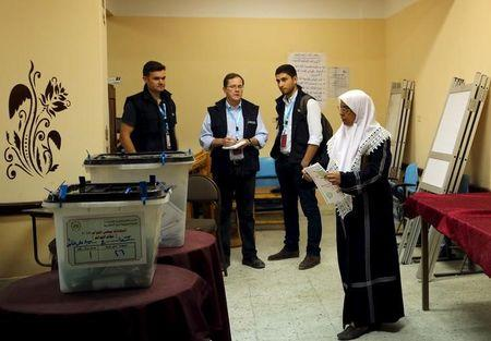 International observers watch a woman cast her vote at a school used as a voting centre in Alexandria, Egypt