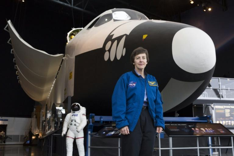 Wendy Lawrence, a retired US Navy captain and former NASA astronaut, stands next to the Space Shuttle trainer that was used for astronaut training, now at the Museum of Flight in Seattle