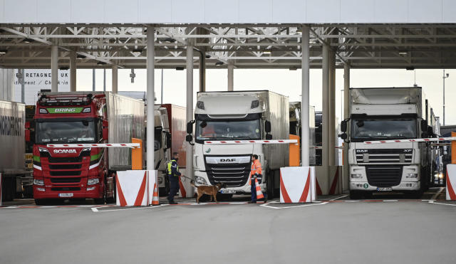 """FILE - In this Tuesday, Sept. 17, 2019 file photo, an employee of Eurotunnel and his dog check trucks on their way to Britain during a day of test in case of no deal Brexit, at the exit of the Channel tunnel in Calais, northern France. Britain's government watchdog says there is still a """"significant amount"""" of work to do to ensure Britain has an adequate medicines supply in case of a no-deal Brexit. In a report issued on Friday, Sept. 27, the National Audit Office said additional shipping capacity chartered by the U.K. for sending goods across the English channel might not be operational until the end of November - one month after the Oct. 31 deadline. (Denis Charlet, Pool via AP, file)"""