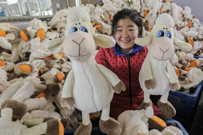 A worker poses with soft toys, manufactured at a toy factory in Lianyungang, eastern China's Jiangsu province (AFP Photo/-)