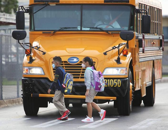 Students wearing masks cross in front of a school bus at Carrie P. Meek/Westview K-8 on the first day back of in-person learning for pre-k, kindergarten and first-graders in Miami-Dade public schools.