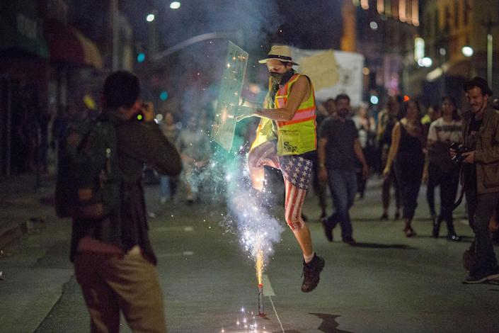 <p>A man jumps over fireworks as people march to protest the upset election of Republican Donald Trump over Democrat Hillary Clinton in the race for President of the United States on Nov. 9 2016 in Los Angeles, Calif. (Photo: David McNew/Getty Images) </p>