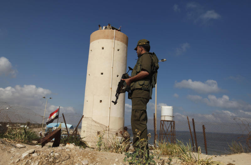 Palestinian Hamas security guard stands near an Egyptian watch tower on the border with Egypt in Rafah, southern Gaza Strip, Friday, July 5, 2013 Egyptian official said the country's border crossing with Gaza Strip in northern Sinai has been closed indefinitely, citing security concerns. The decision comes hours after suspected Islamic militants attacked four sites in northern Sinai, targeting two military checkpoints, a police station and el-Arish airport, where military aircraft are stationed. (AP Photo/Hatem Moussa)