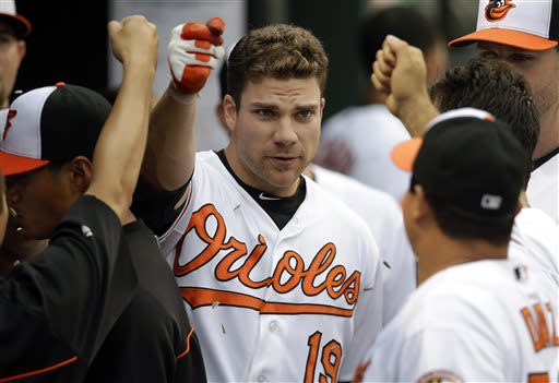 Baltimore Orioles' Chris Davis, center, is greeted by teammates in the dugout after hitting a solo home run in the second inning of a baseball game against the Texas Rangers, Thursday, July 11, 2013, in Baltimore. (AP Photo/Patrick Semansky)