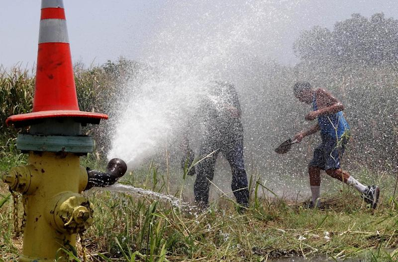 Pedro Alcozer, right, and Victor Pena refresh themselves in the water shooting from a fire hydrant at Somerset Road and Fairmeadows on Wednesday, June 27, 2012. San Antonio Water System has been opening hydrants to let water run in an attempt at preventing water in two area storage tanks from declining in quality due to the summer heat. (AP Photo/San Antonio Express-News, Billy Calzada) MAGS OUT NO SALES SAN ANTONIO OUT