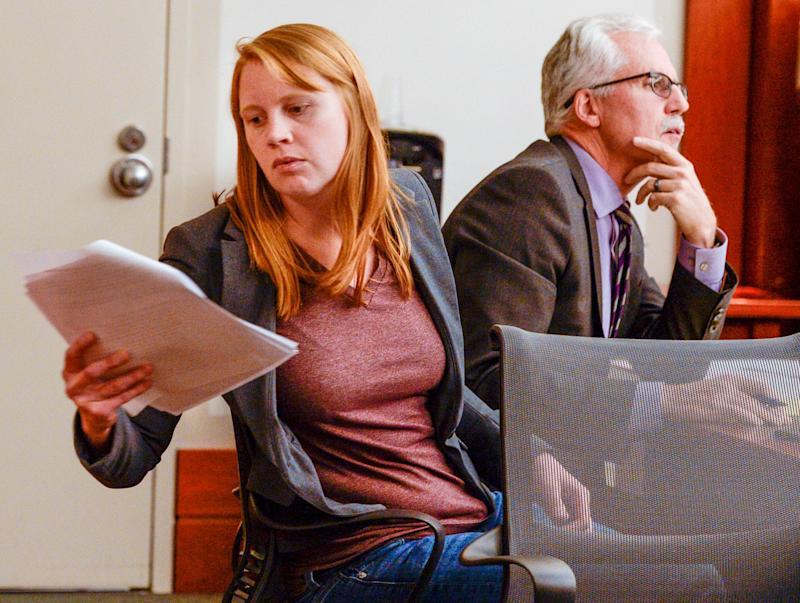 Tilli Buchanan, left, reads a document in court as she sits with Randy Richards, right, her lawyer  (Photo: AP)