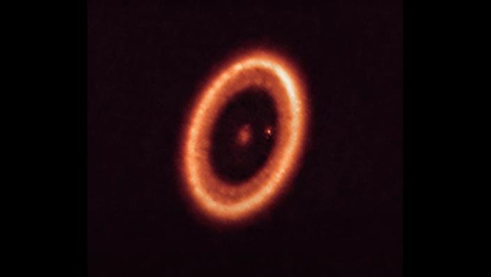 A telescopic image of a planet surrounded by ring of dust and gas, as well as a moon that itself is surrounded by its own ring of dust and gas.