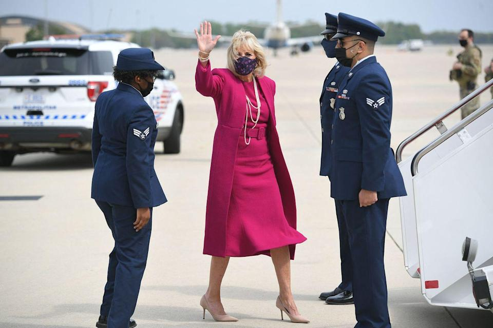 <p>The First Lady chose a matching raspberry-colored belted dress and coat to visit New Mexico and Arizona. She paired the look with long pearl strands, nude pumps, and a patterned mask. </p>