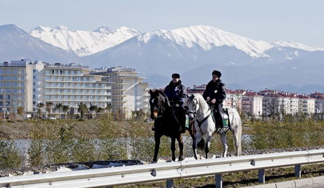 Two police officers patrol on horses near the Olympic Park in Sochi