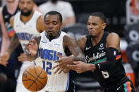 Orlando Magic forward Gary Clark (12) and San Antonio Spurs guard Dejounte Murray (5) scramble for the ball during the second half of an NBA basketball game in San Antonio, Friday, March 12, 2021. (AP Photo/Eric Gay)